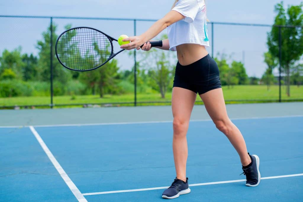 Woman Wearing Black Shorts And White Crop Top Holding Tennis 2694942